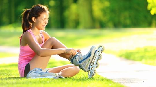 Frau sitzt im Park und zieht Ihre Inlineskater an.